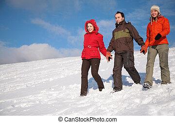 three friends walk on snow on hillside 2