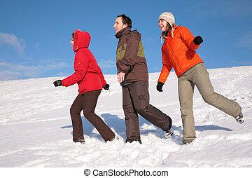 three friends walk on snow on hillside