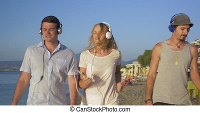 Three friends walking with music on the beach