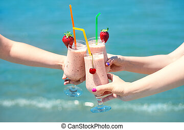 Three fruit juice smoothie in classic glass cups of berry fruits turquois sea water background. Three girls cheers