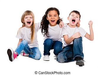 three funny trendy children laugh sitting on the floor