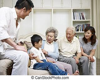 three-generation asian family talking in living room.