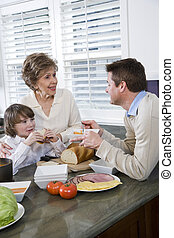 Three generation family in kitchen eating lunch, talking and...