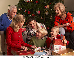 Three Generation Family Opening Christmas Gifts At Home