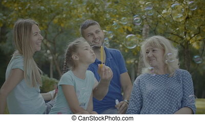 Three generation family playing with soap bubbles