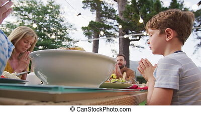 Three generation family praying before having lunch outdoors...