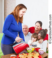 family drinks tea with cakes at home