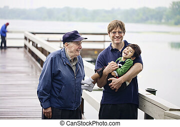 Three generations interacting together on the dock on misty...