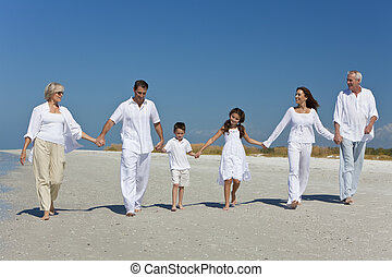 Three Generations of Family Walking Holding Hands on Beach...