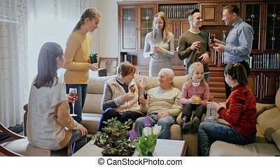 Happy large family gathered in parental home for family party, cheerfully talking in cozy living room
