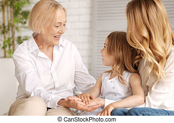 Three generations of women holding hands together