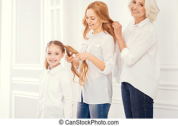 Three generations of women making hairstyles