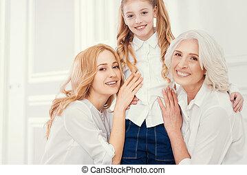 Three generations of women posing for camera