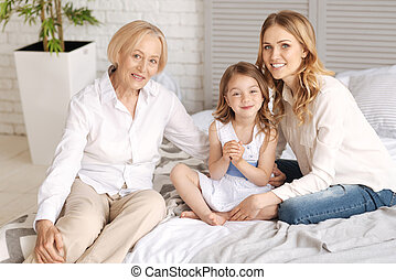 Three generations of women sitting on one bed