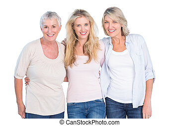 Three generations of women smiling at camera on white...