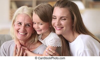 Three generations women happy family having fun embracing...