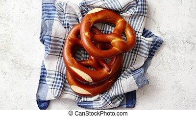 Three german fresh baked pretzel buns placed on napkin -...