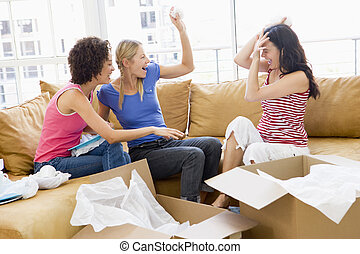 Three girl friends playfully unpacking boxes in new home smiling