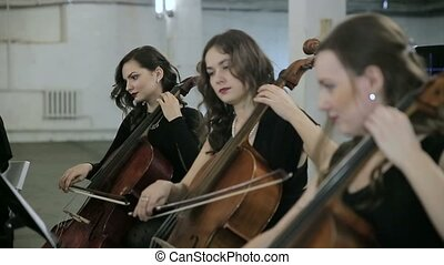 Three girl play on violoncello in orchestra.