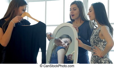 Three girlfriends at the mirror looking at her dress
