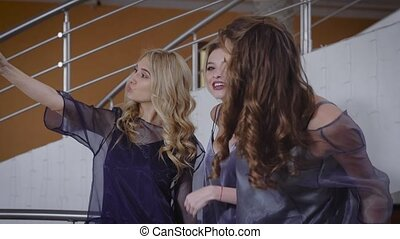 Three girlfriends indoors. Girls very beautifully look. The company of girls are ready to a magnificent party. Before an exit two fair-haired and the brunette take a selfie.