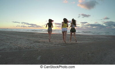 Three girlfriends running on a sandy beach towards the sea and playing with their feet in the water