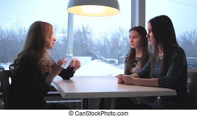 Three girlfriends talking in cafe in the winter