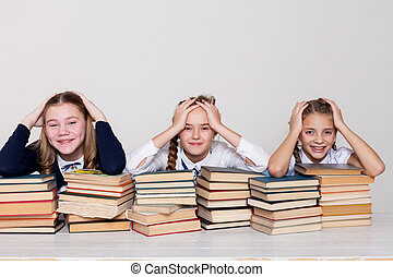 three girls at school with lots of books
