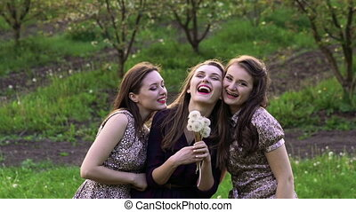 Three girls blowing dandelions in the garden. Slowly