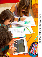 Three girls busy with homework. - Three teenage girls busy...