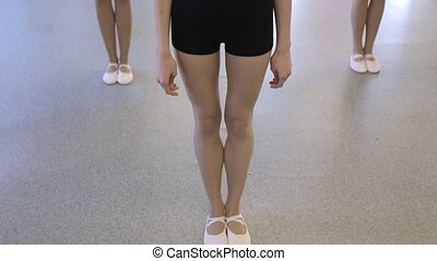Three girls dressed in same black costumes stands in dancing studio