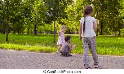 Three girls eating bananas during a walk in the park at...