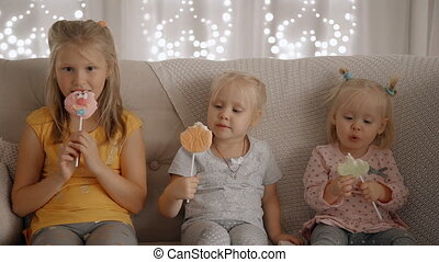 Three girls eating lollipops sitting on sofa in cozy apartment.