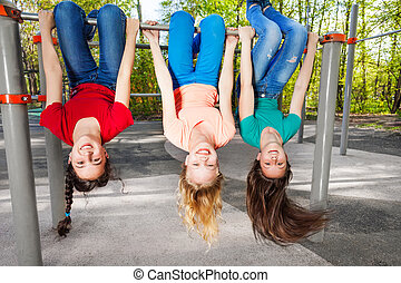 Three girls hanging upside-down on brachiating bar