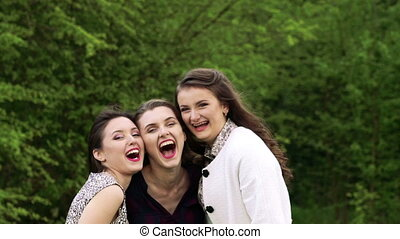Three girls in embrace smiling and looking at a camera. Slowly