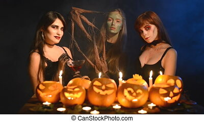 Three girls in Halloween costumes and makeup with pumpkins...