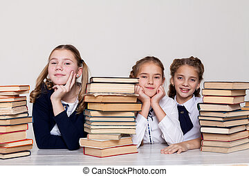three girls in the classroom studying many books