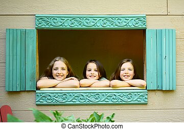 Three girls looking out dollhouse window