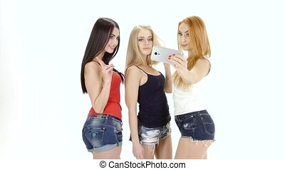 Three girls of model appearance make selfie to camera...