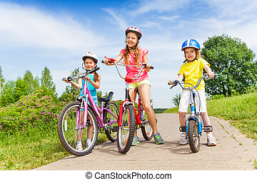 Three girls on a paved road stand holding with bicycles on sunny summer day