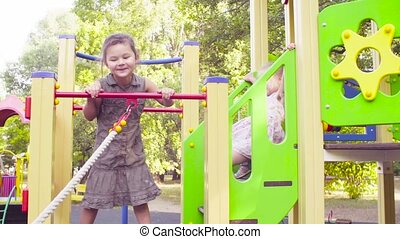 Three girls on a play complex on the playground. One is...