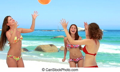 Three girls passing the inflatable beach ball near the water