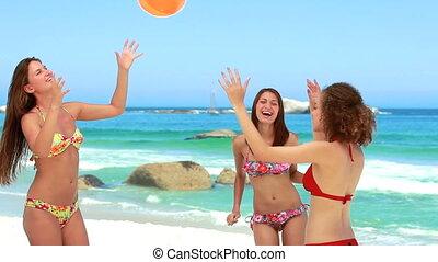 Three girls passing the inflatable beach ball