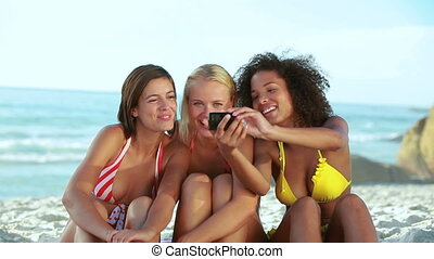 Three girls posing for a photo at the beach