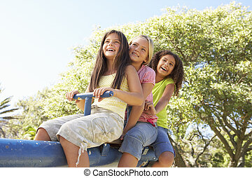 Three Girls Riding On See Saw In Playground