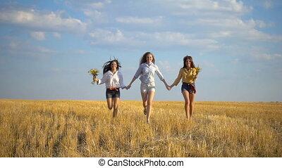 Three girls running on stubble field, slow motion - Three ...