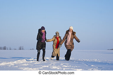 Three girls running on the snowy field