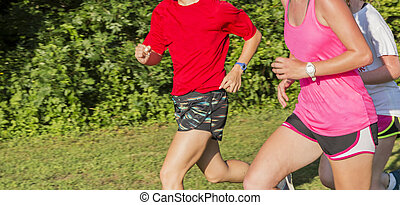 Three girls running together in a park