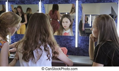 Three girls sit in front of mirror and happily talk with each other.