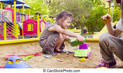 Three girls sitting in a sandbox and picking up sand - Crane...